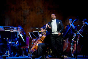 A man stands in full black tie singing in front of the cellos and double basses of the orchestra