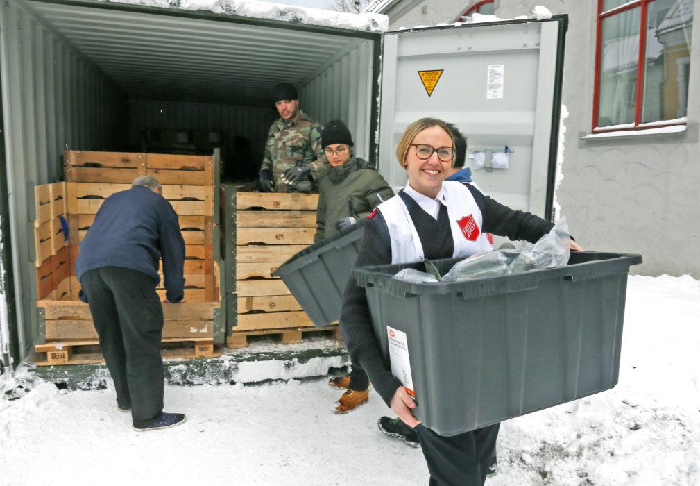 En smilende frelsesoffiser ser i kameraet og bærer matkasse fra det nederlandske forsvaret.