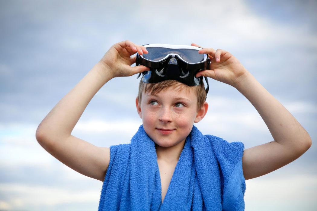 gutt med svømmebriller. Blått håndkle rundt skuldrene.