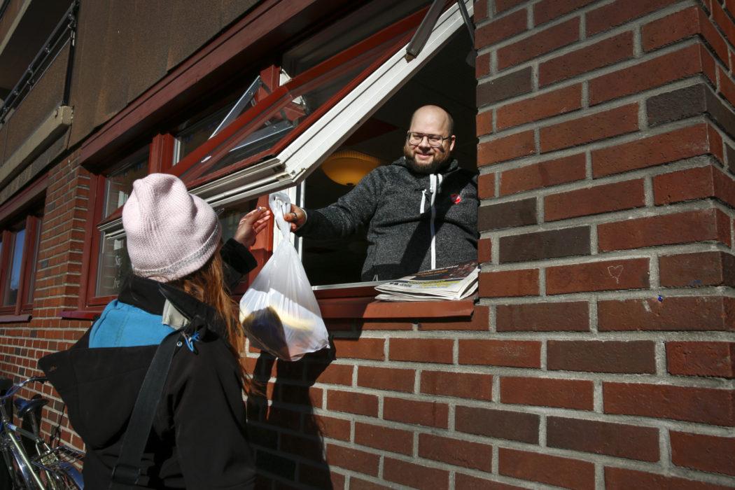 en smilende mann gir ut matpose gjennom vinduet på Fyrlyset under koronakrisen mars 2020