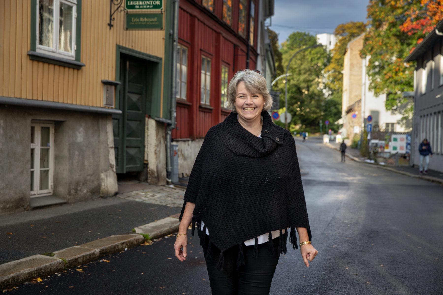 En smilende dame går mot kamera. i Bakgrunnen ser vi en Oslogate med trehus i friske farger.
