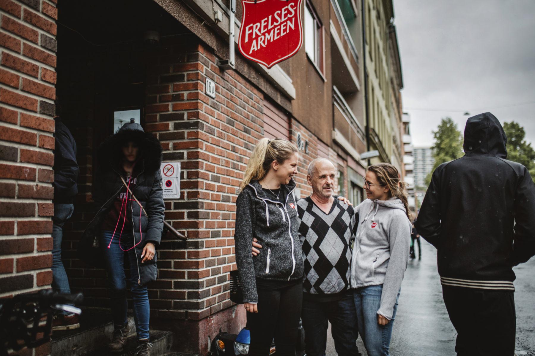 En mann står og holder rundt to ansatte ved Fyrlyset i Oslo.