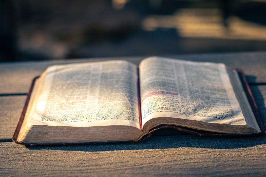 Oppslått bibel på et bord ute, sollys