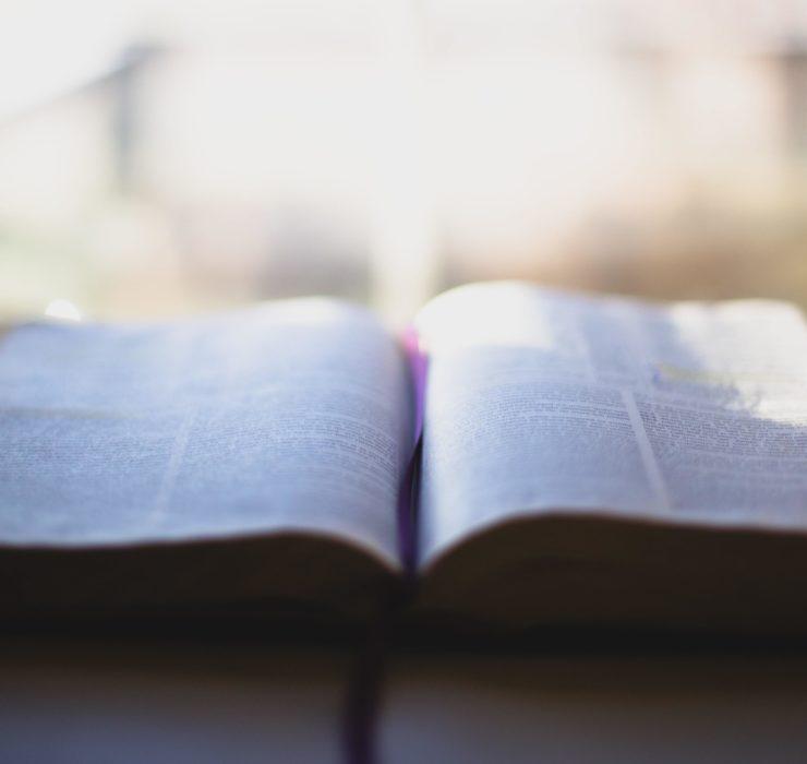 En oppslått bibel med lys, uklar bakgrunn