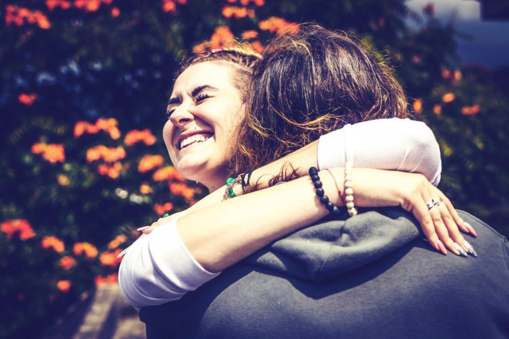 Smilende jente gir en klem til en man ser ryggen på. Utendørs, sol.