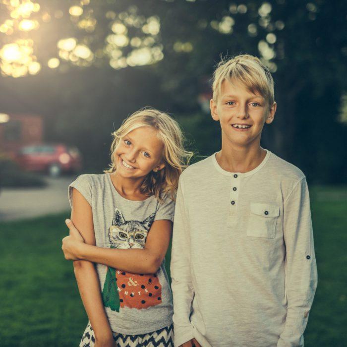 Jente og gutt smiler til kamera