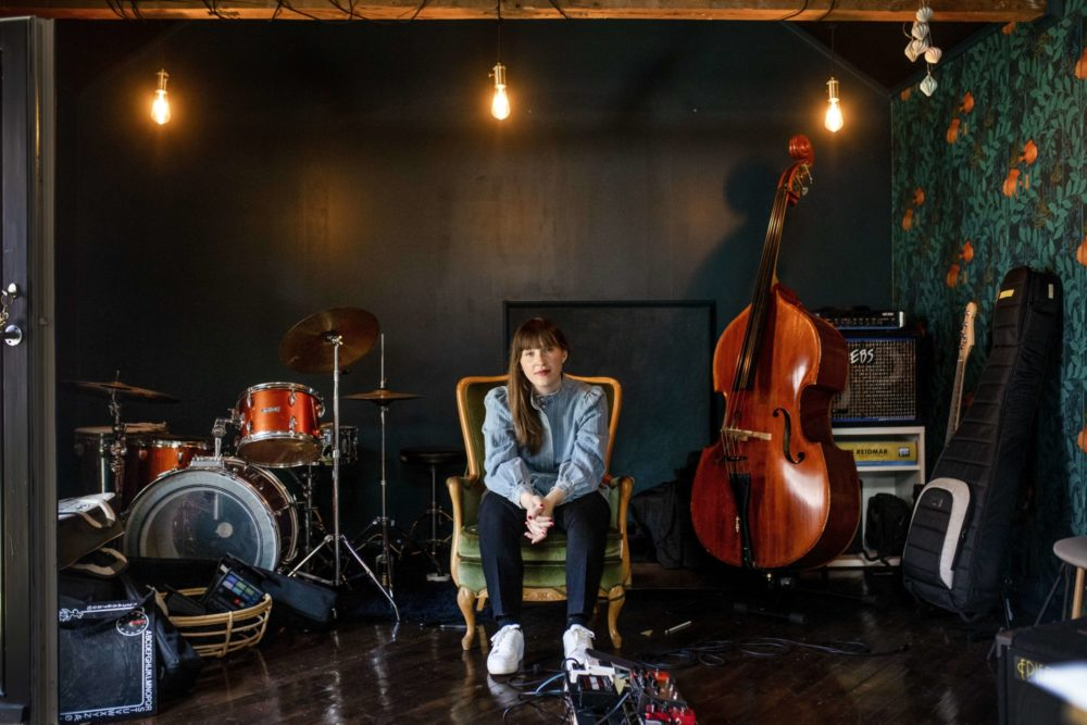 Ellen Andrea Wang sitter i en lenestol mellom et trommesett og en kontrabass. Hun smiler til fotografen.