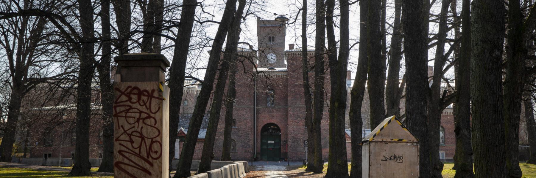Bildet er tatt ved porten til veien som leder til inngangsdøren til Oslo fengsel. Sollyset titter frem mellom de bladløse trærne.
