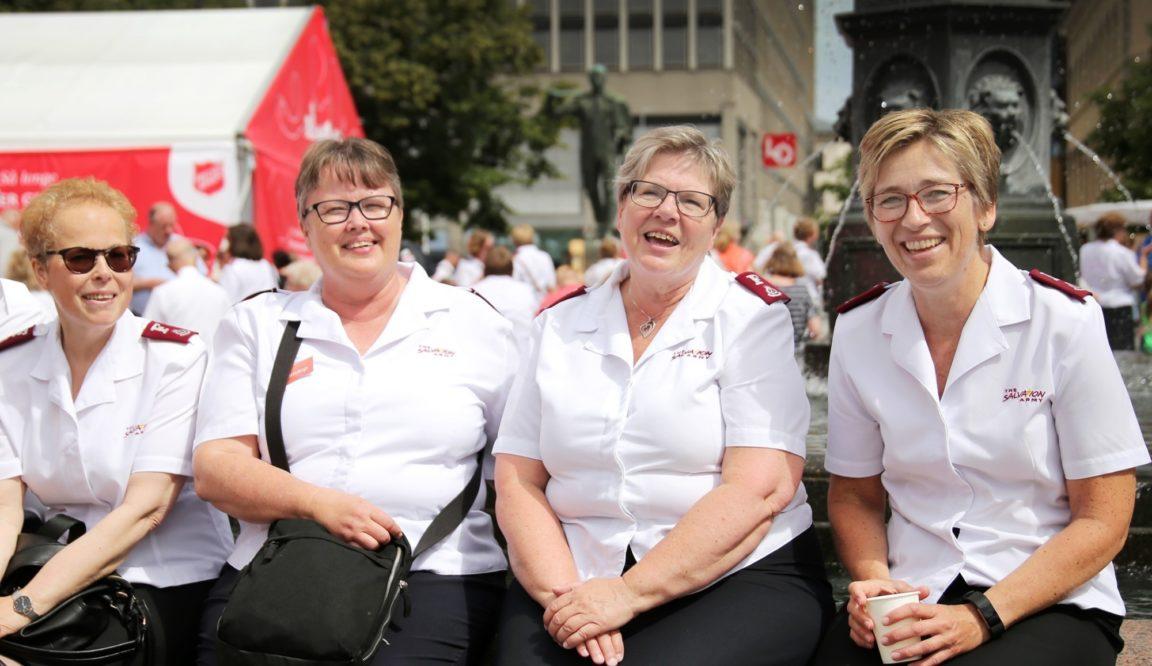 4 kvinner sittende i uniform smilende i sola