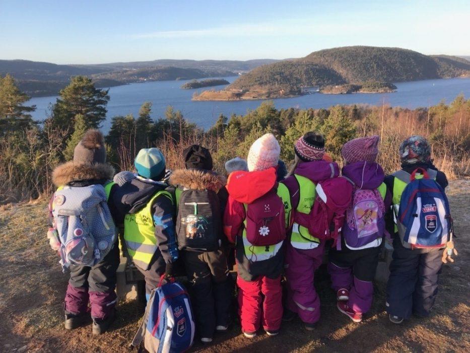 Barnehagebarn som står og ser utover fjorden