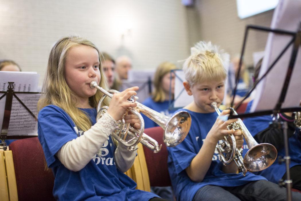 En jente og en gutt sitter og spiller på hvert sitt instrument