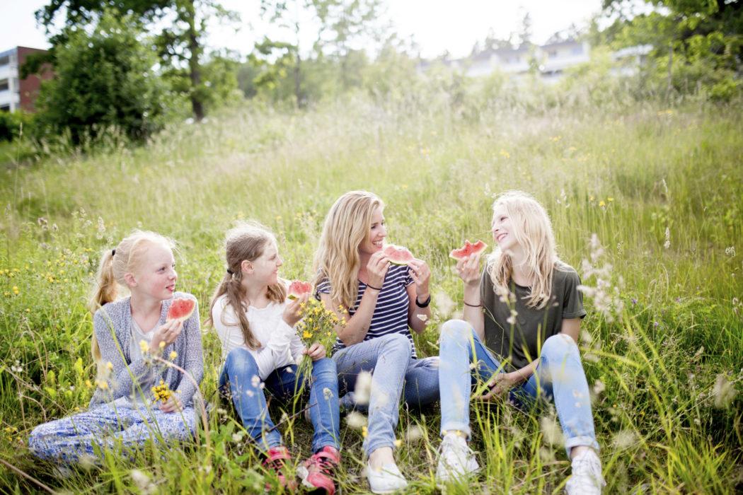 4 jenter i ulik aldre sitter i blomstereng og smiler og spiser vannmelon