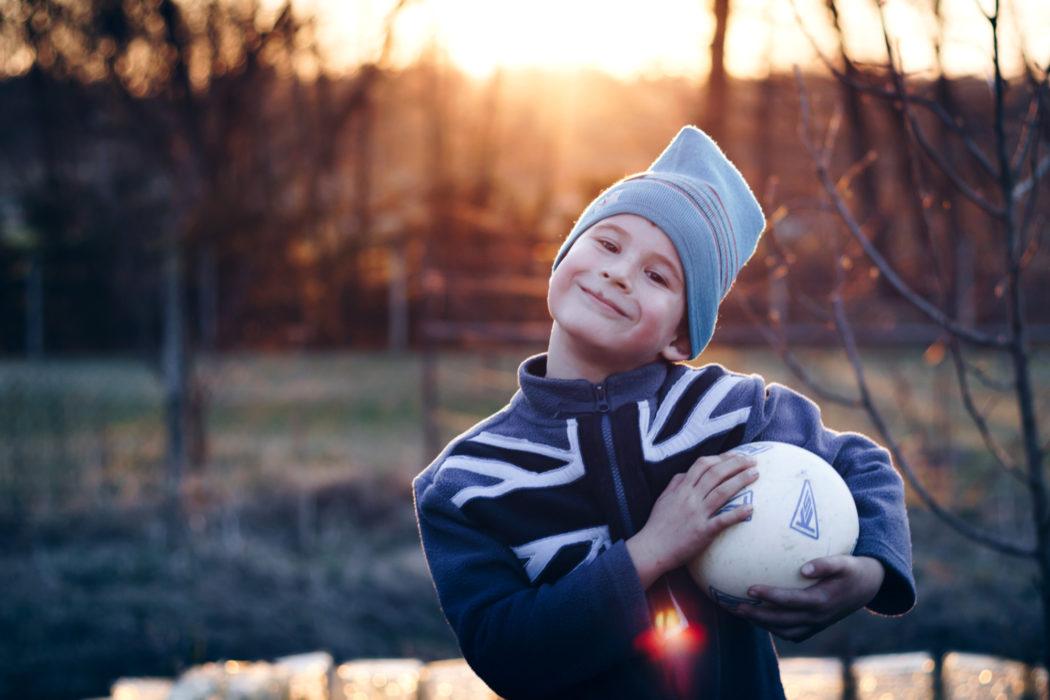 gutt med fotball venter på fosterforeldre