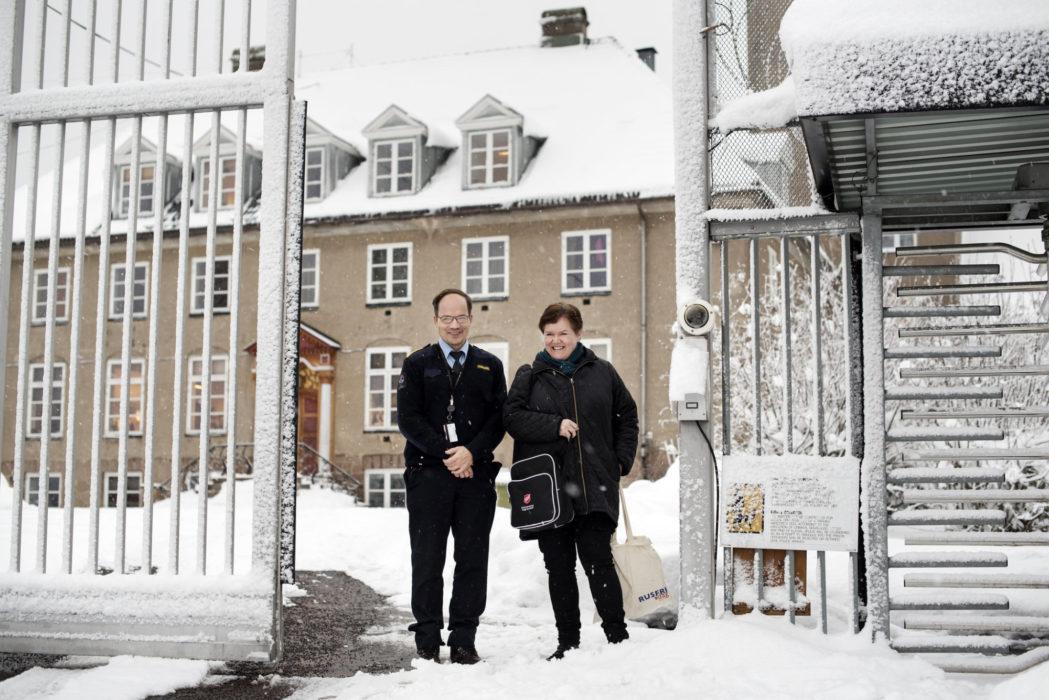 Dame fra Frelsesarmeen og uniformert mann står ved inngangsporten til et fengsel.