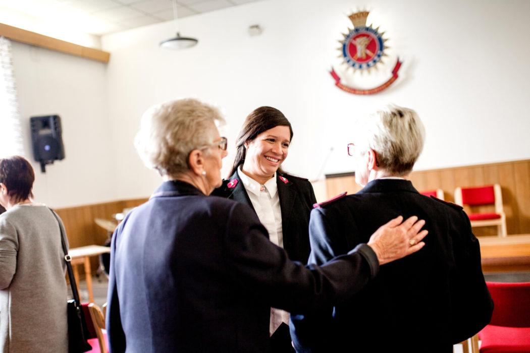 Damer i møtelokale i Frelsesarméuniform, smilende