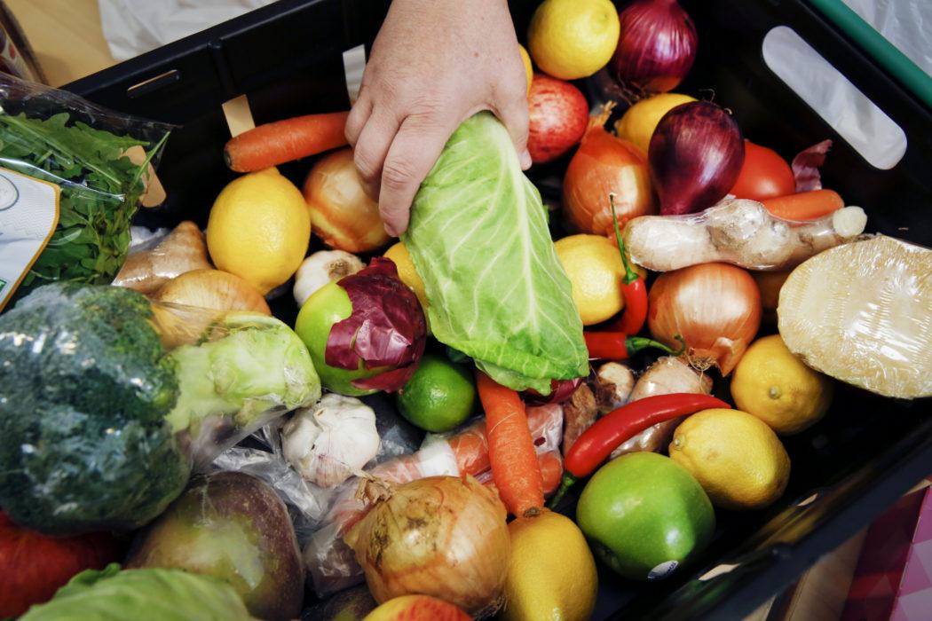 Kasse med grønnsaker, en hånd holder i en salat