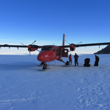 People load equipment onto a red aeroplane that has landed in the middle of the snowy Antarctic tundra.