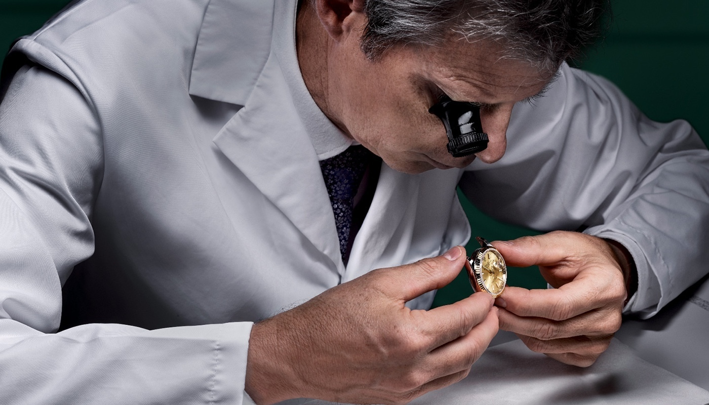 Man inspecting a Rolex watch for servicing