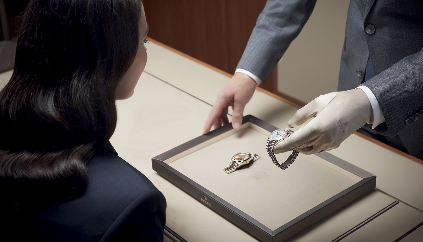 A woman looking at a Rolex watch that has been serviced
