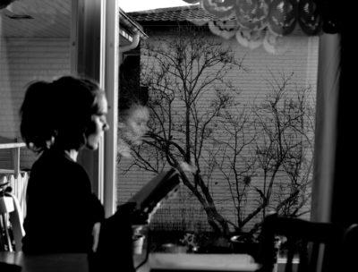 Ulrika Nettelblad läser en bok, svartvitt, framför ett fönster.