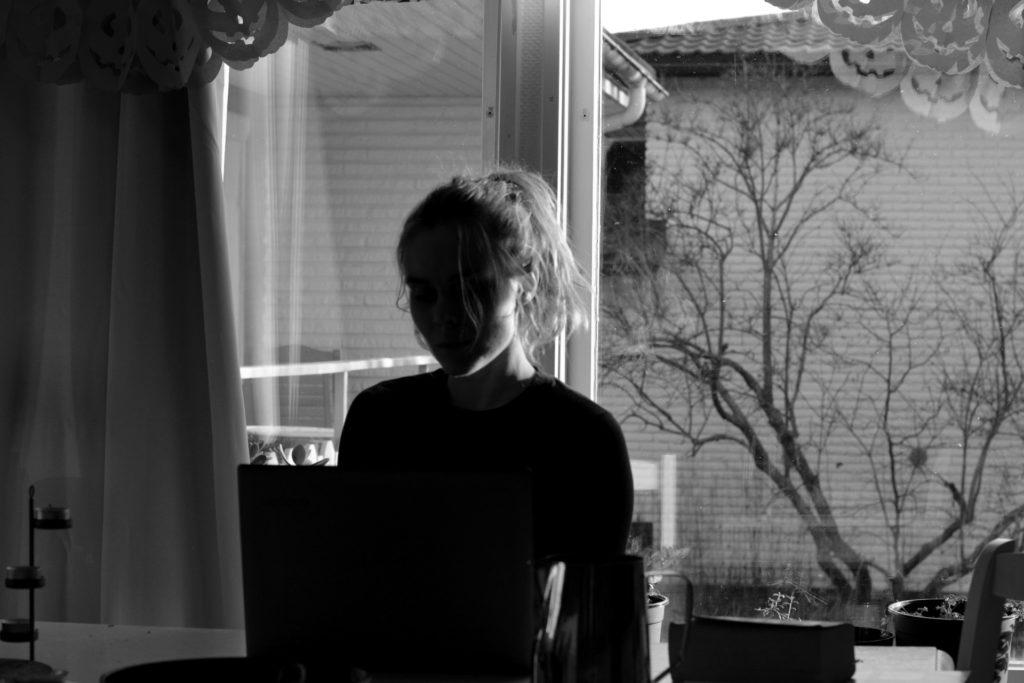 Svartvit bild på Ulrika Nettelblad som skriver på laptop i motljus.