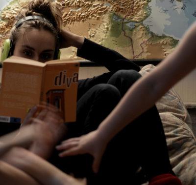Mamma med hörselskydd läser Diva av Monika Fagerholm omgiven av barn. Karta i bakgrunden.