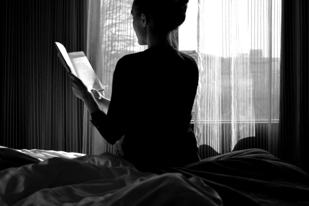 Ulrika Nettelblad läser bok på Hotell Pommern. Svartvit bild, motljus.