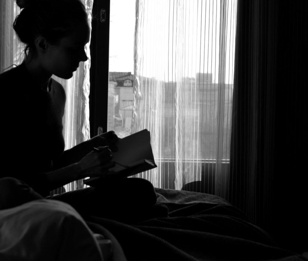 Ulrika Nettelblad läser bok på Hotell Pommern. Svartvit bild, motljus, silhuett.