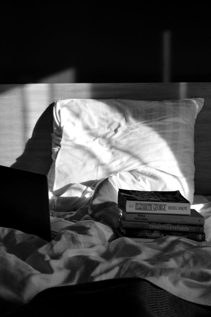 Hög med böcker och laptop på hotellsäng på Hotell Pommern. Svartvit bild.