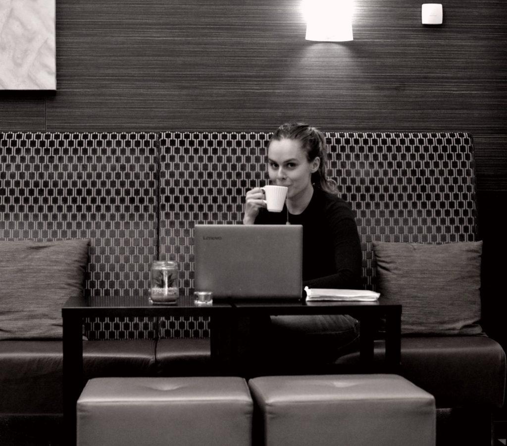 Ulrika Nettelblad med tekopp i handen i hotellobbyn på Hotell Lobbyn. Laptop på bordet.