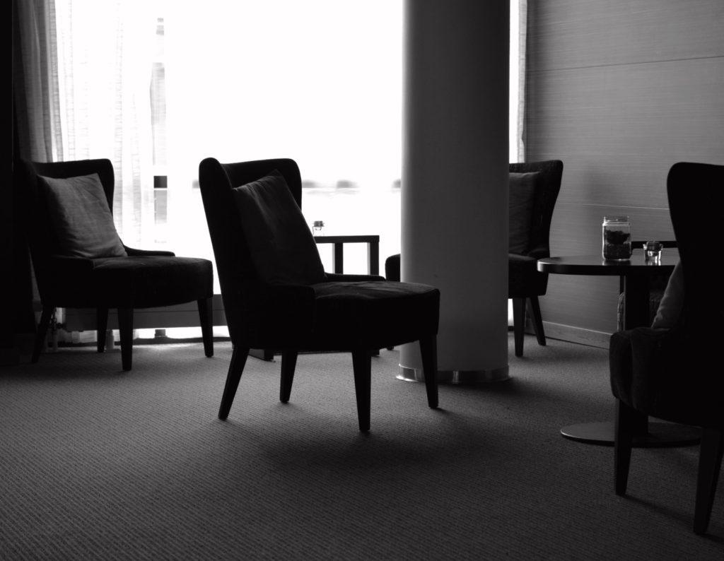 Svartvit bild, motljus på bord och fåtöljer på Hotell Pommern.