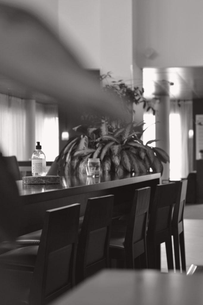 Svartvit bild med sepiatoner på bord, stolar och handsprit i lobbyn på Hotell Pommern.