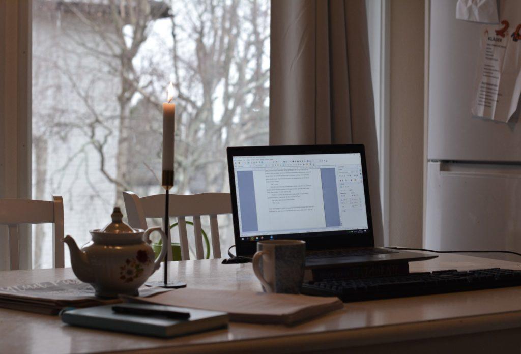 Laptop, tekanna, romanmanus utskrivet på papper på köksbord framför fönster.