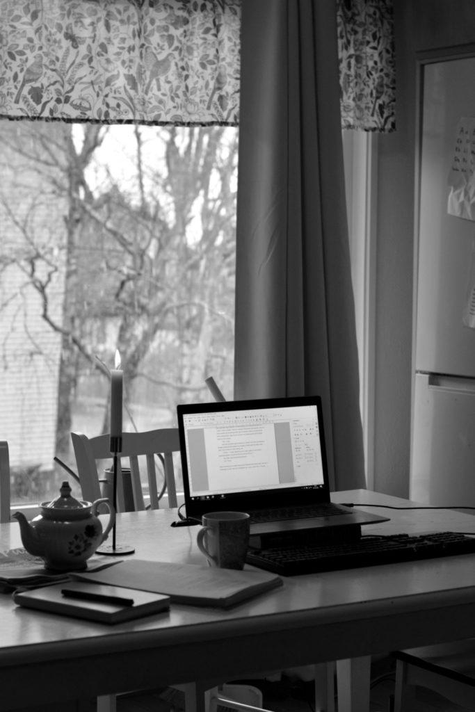Laptop, tekopp, tekanna, romanmanus och anteckningsbok och levande ljus på köksbord framför fönster. Svartvit bild.