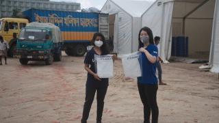 Srabasti Sarker from the Logistics Sector and Sua Choi from WFP holding JTS gowns upon their arrival at the Cox's Bazar COVID-19 Special Hub. Photo: WFP/Brook Dubois