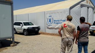 Two men survey a Logistics Cluster mobile storage unit in Iraq