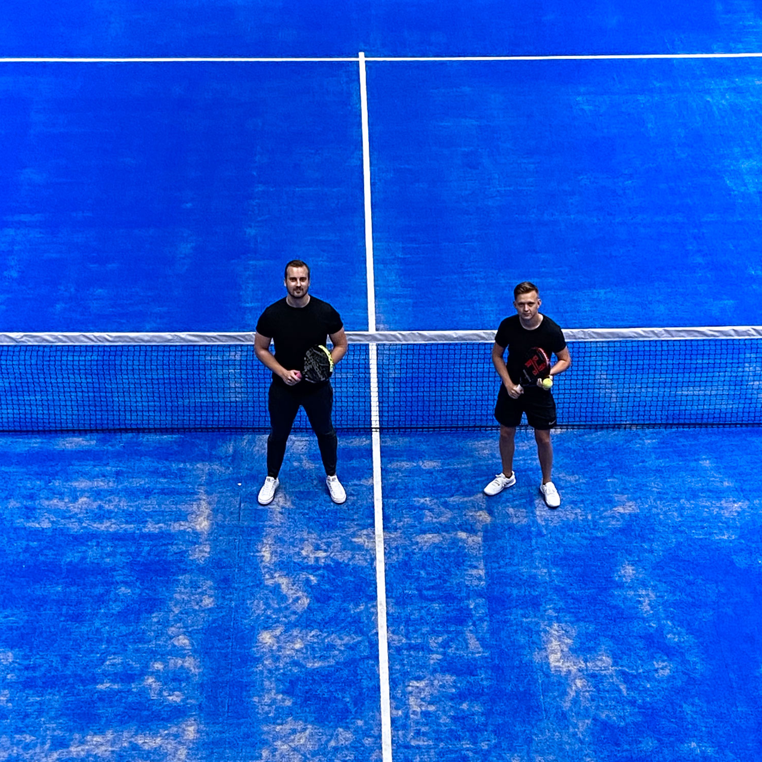 Two men on a blue padel court