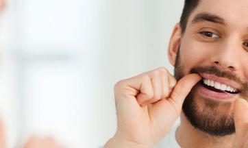 Mann mit Zahnseide vor Spiegel
