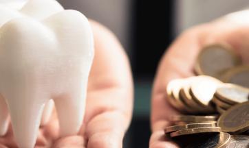 Zahn in einer Hand, Geldmünzen in anderer Hand