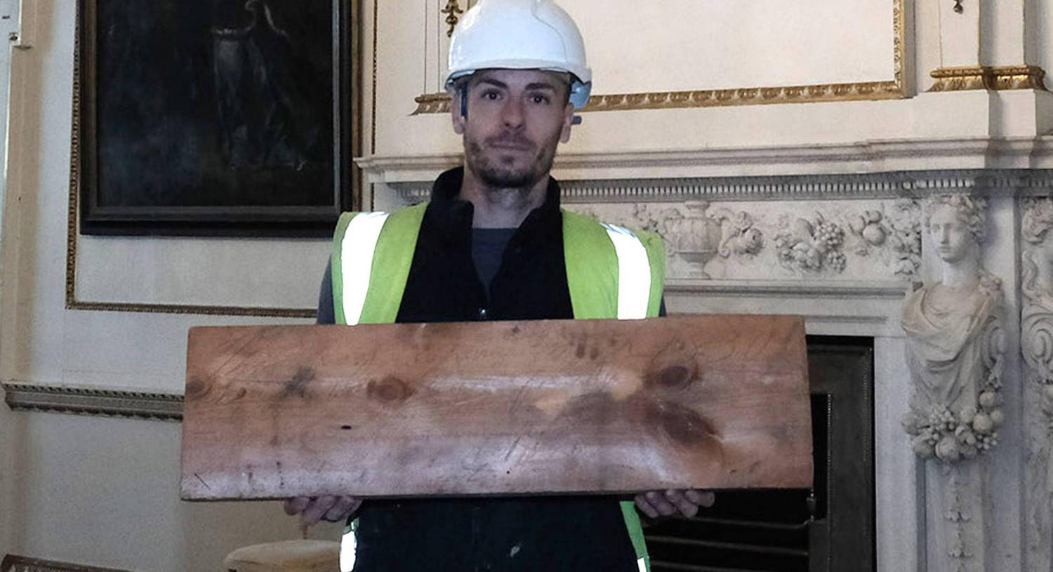 Joe Hutchinson, in Wentworth Woodhouse, holding an uncovered roof board with an inscription etched into it from 1830, they are in the Van Dyk room where the board was found in the roofspace above them. Picture: PA