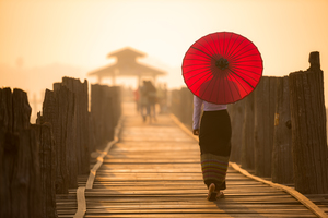 Burmese woman with umbrella on U Bein Bridge, Mandalay, Myanmar