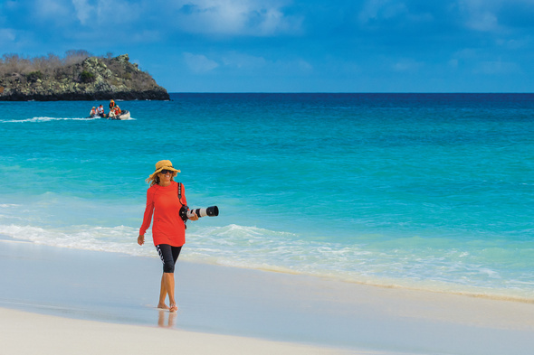 Lindblad Expeditions guest in the Galapagos with a camera and sunhat