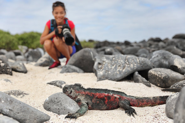 A tourist in the Galapagos with a camera, a key item on your cruise packing list