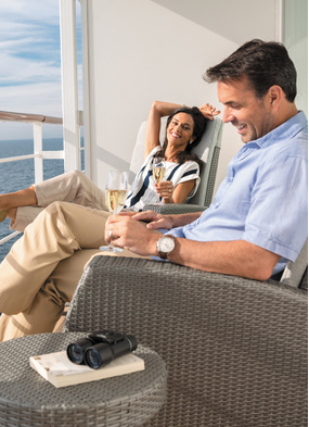 Regent guests relaxing on the balcony of one the best cruise ship suites at sea
