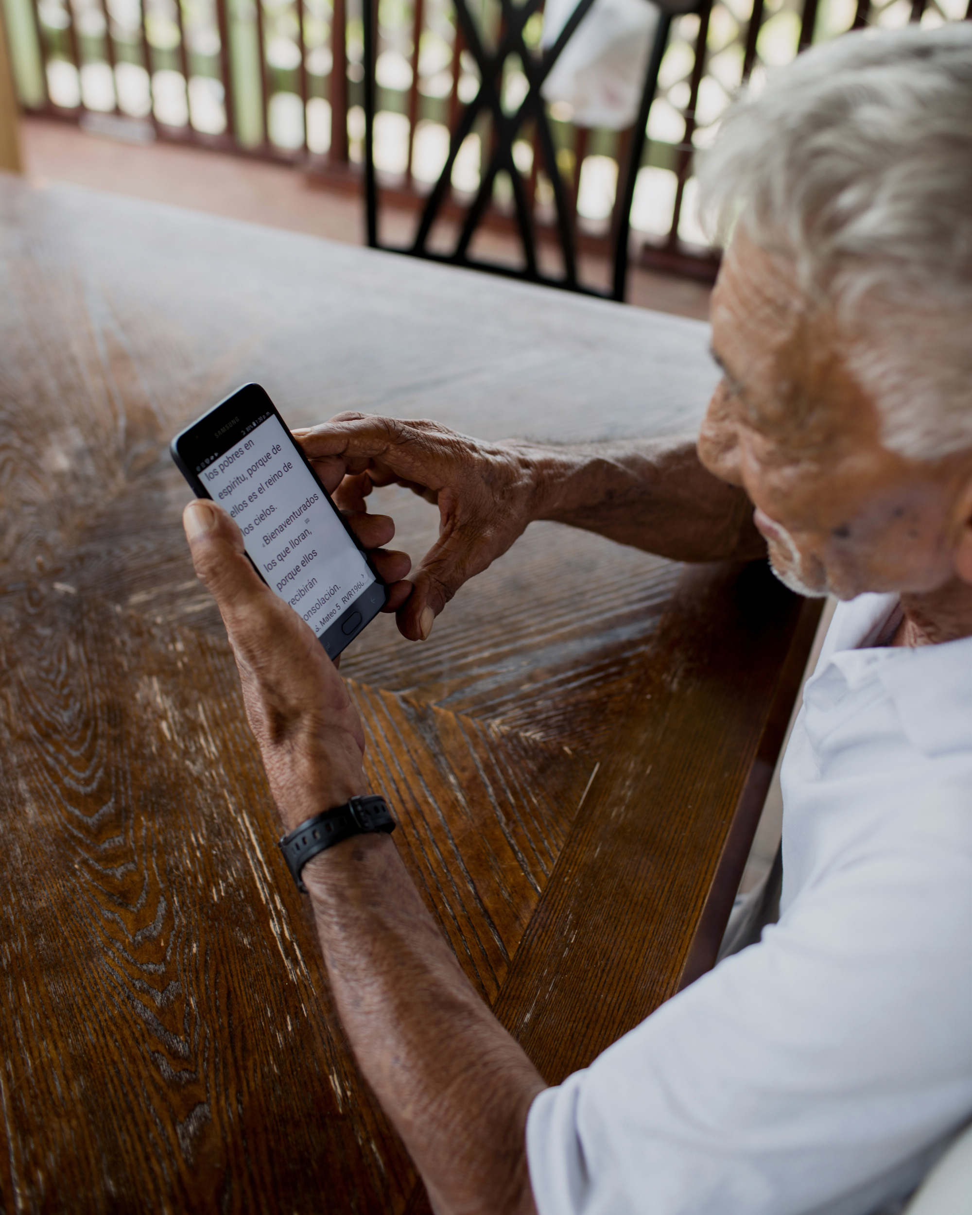 Foto av eldre mann som bruker digital tjeneste på mobilen