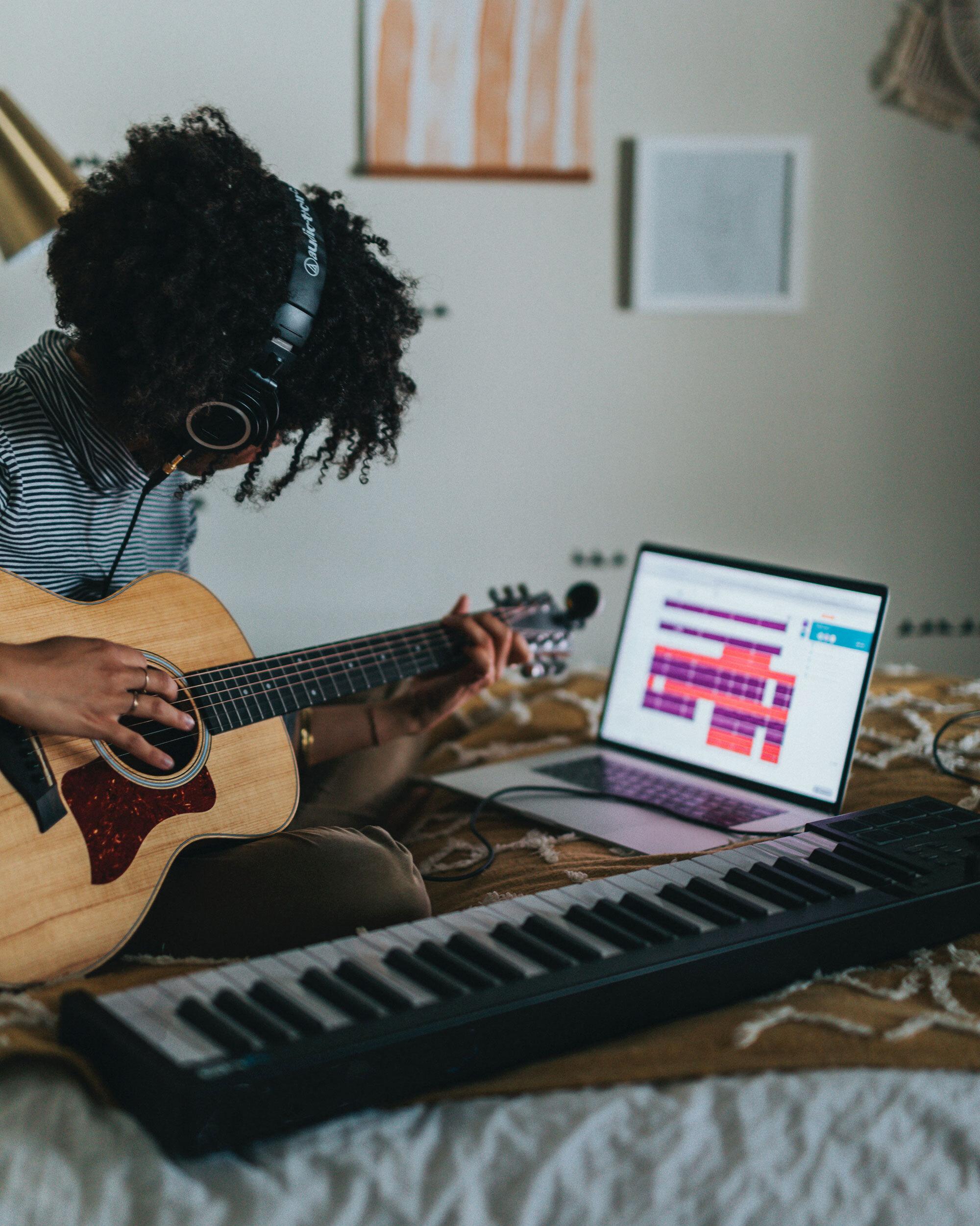 Foto av jente som sitter på senga og spiller inn gitar