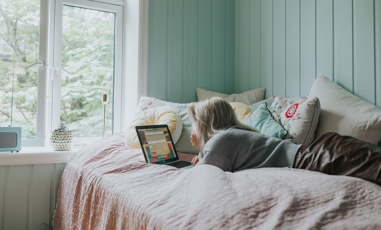 Foto av jente som ligger på senga og kjøper flybillett
