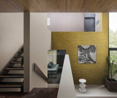 Staircase in a contemporary home. Eyecatching yellow Aruba wallcovering in banana yellow. Black-and-white work of art.