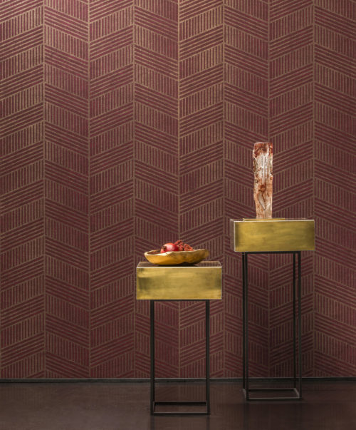 Vivid red and gold art deco wallcovering. Two golden tables. One with a white and red artwork. One with a tray with a pomegranate.