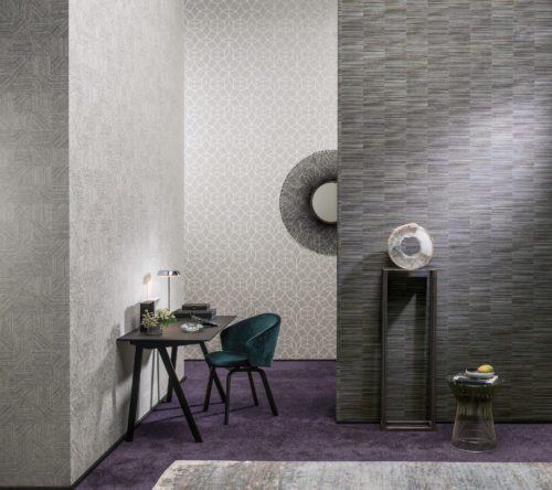 Interior in grey tones. Decor for 3 different Avenue wallcoverings by Omexco. Round details: a mirror, an artwork and a little table. On the lefthand side a black desk with trinkets.